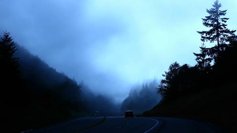 Traffic passes as fog rolls past a forested mountain top Stock Video Footage