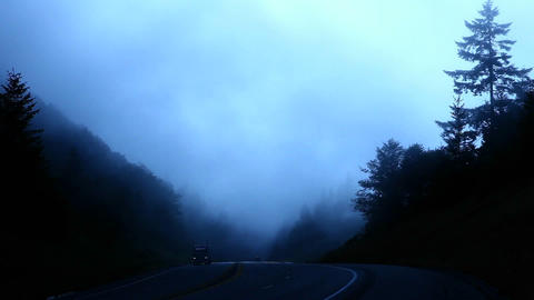 Traffic passes as fog rolls past a forested mountain top Footage
