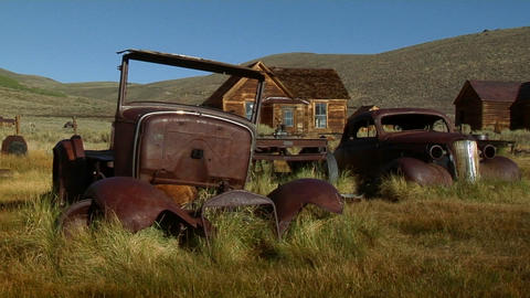 Old rusting cars sit near an abandoned building in the ghost town of Bodie Footage