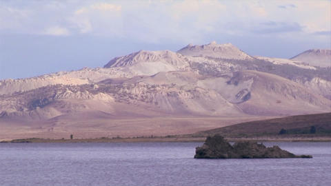 Birds soar over Mono Lake with the extinct volcano in the... Stock Video Footage