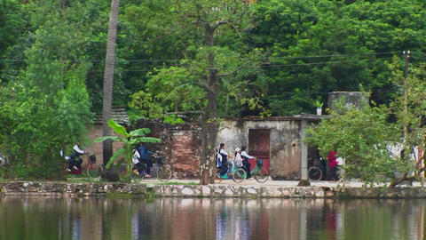 Girls ride their bicycles beside a lake in Vietnam Stock Video Footage