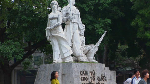 Citizens in Hanoi play badminton in front of a public statue Stock Video Footage