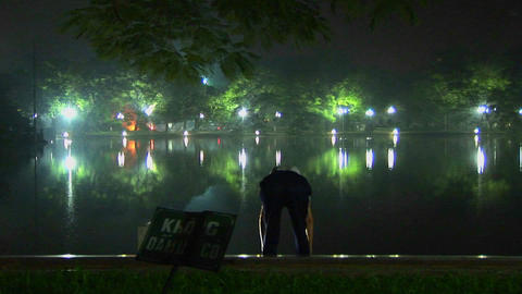 An old man does tai chi exercises in front of a lake in... Stock Video Footage