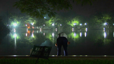 An old man does tai chi exercises in front of a lake in Hanoi Vietnam Footage