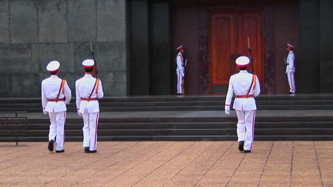 Vietnamese guards walk in front of the tomb of Ho Chi Minh Footage