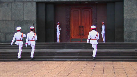 Vietnamese guards walk in front of the tomb of Ho Chi Minh Stock Video Footage