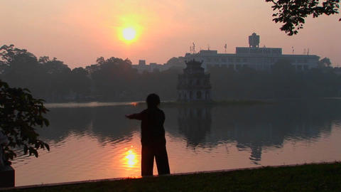 A woman practices tai chi in front of a lake in Hanoi,... Stock Video Footage