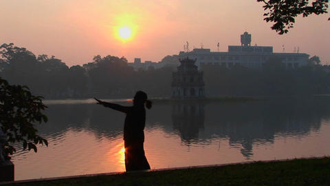 A woman practices tai chi in front of a lake in Hanoi, Vietnam Footage