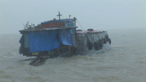 A dilapidated vessel heads out into a heavy storm Stock Video Footage