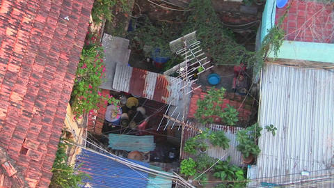 Pull back from a woman working on a rooftop to reveal a small Vietnamese neighborhood Footage