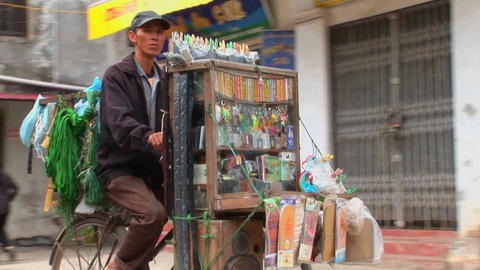 A man pedals a bicycle loaded with medicine and other goods down a narrow street in Vietnam Footage