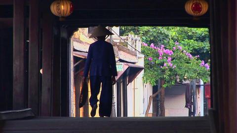 A woman walks under a bridge in a small village in Vietnam Stock Video Footage