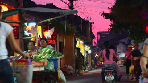 Vendors wheel their wares out at dusk in a Vietnamese village Footage