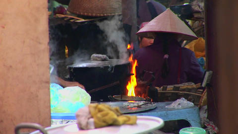 Fires burn and a pot boils as Vietnamese villagers... Stock Video Footage