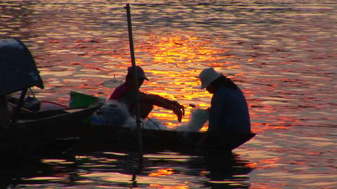 Vietnamese fishermen head out in their canoe at dusk Footage