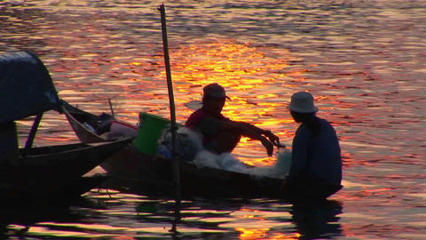 Vietnamese fishermen head out in their canoe at dusk Stock Video Footage