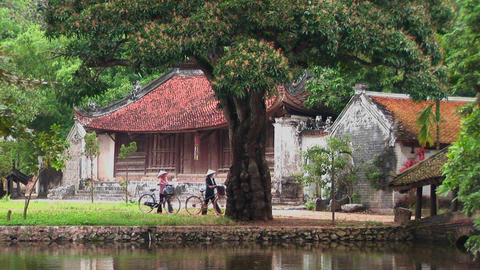 People walk their bicycles past a temple in Vietnam Stock Video Footage