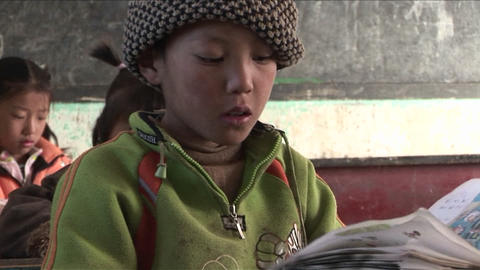 Children practice writing in a rural classroom in China Footage
