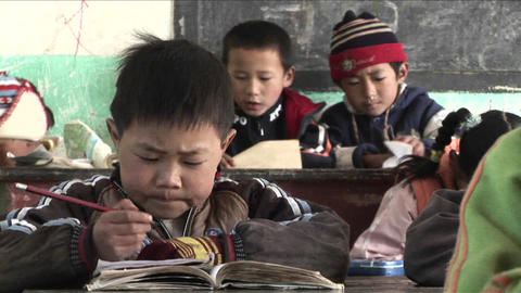 Children practice writing in a rural classroom in China Stock Video Footage