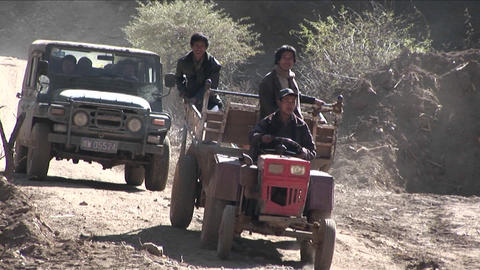 Men drive a primitive tractor across a rural landscape in... Stock Video Footage
