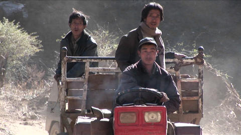 Men drive a primitive tractor across a rural landscape in China Footage