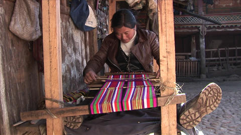 A woman operates a basic loom in a Chinese village Stock Video Footage