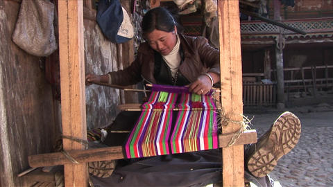 A woman operates a basic loom in a Chinese village Footage
