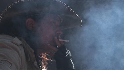 A Chinese cowboy sits by a fire and smokes Stock Video Footage
