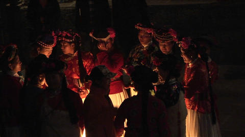Ethnic Chinese gather around a fire at night for a ceremony Footage