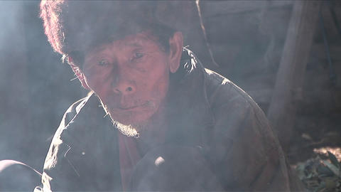 An old Chinese man looks through a cloud of smoke Footage