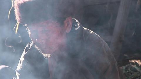 An old Chinese man looks through a cloud of smoke Stock Video Footage