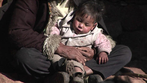 A small child sits in a poor beggars arms Stock Video Footage