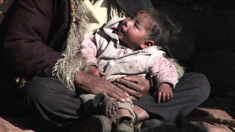 A Small Child Sits In A Poor Beggars Arms stock footage