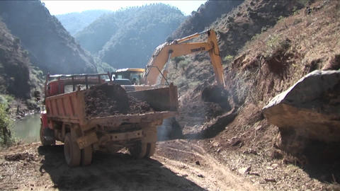 A steam shovel moves earth into a dump truck along a... Stock Video Footage