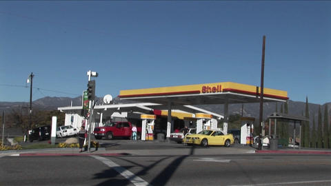 A time lapse shot of a gas station as traffic moves quickly by Footage