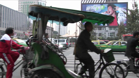 Large amounts of traffic pass by on a Beijing China street with modern billboards in the background Footage