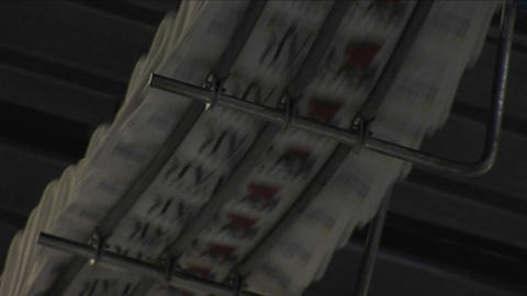 Newspapers move along an assembly line at a factory Footage