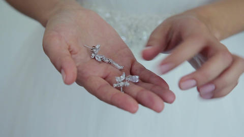 Bride is holding a silver earrings Footage