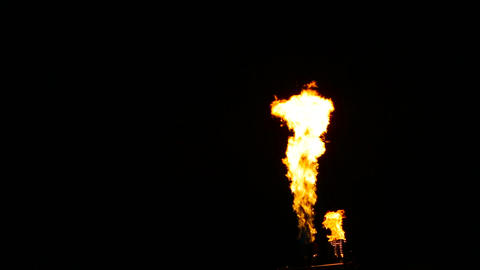 Flames erupt from the turn of two gas burners on a dark background Footage