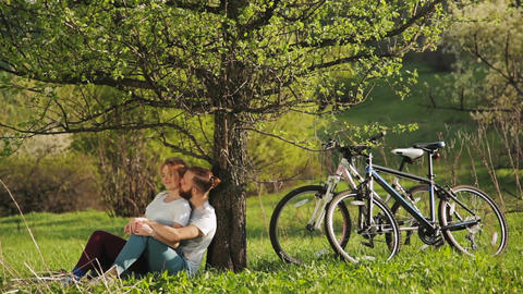 Cyclists man and woman sat down to rest GIF