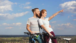 Man and woman with bicycles on a hill watching the sunset GIF