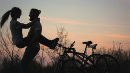 Silhouette of a loving couple at sunset GIF