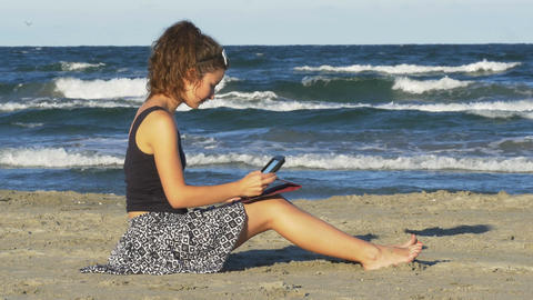 Beautiful young woman sitting on the beach and tipping on her tablet pc on a sum Footage