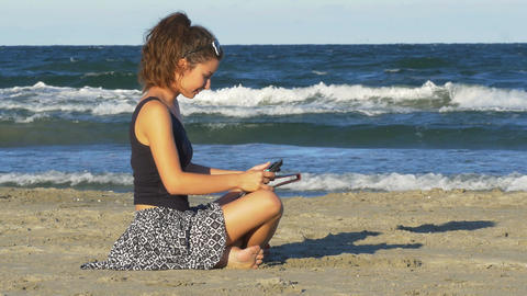 Pretty Caucasian woman having fun with her tablet pc by the sea Footage