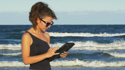 Beautiful girl working on her tablet pc by the sea Footage