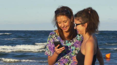 Enthusiastic friends hugging and looking at a smart phone with the sea behind Footage