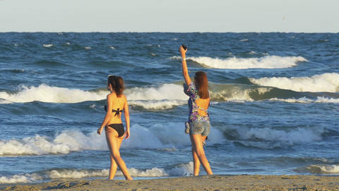 Two young beautiful women in swimsuit taking pictures with smart phone and havin Footage