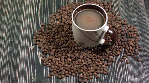 Cup of coffee and grains on table on dark background, fragrant hot drink Footage