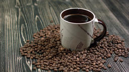 Close-up of coffee cup with roasted coffee beans on wooden background Footage