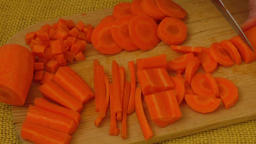 Close up on woman's hand slicing carrot on cutting board Footage